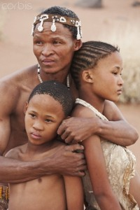 Namibia --- Bushman/San People. Farther embracing his children. Archaeological evidence suggests that they have lived in Africa for at least 22, 000 years. Namibia. N/a?an ku sê (www.naankuse.com) an organization owned by Doctor Rudie van Vuuren and his wife Marlice van Vuuren, one of Namibia's most popular nature conservationists who is fluent in Khoi San, do a lot of work with the bushmen. Amongst others they have the Lifeline Clinic and Bushman School to tend to the needs of the bushmen. This image, as part of a series, was taken to raise awareness and funds for the conservation projects of N/a?an ku sê, as the bushmen had a very close relationship to animals in the past. --- Image by © Martin Harvey/Corbis